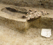 Pit where pottery was discarded in bulk, and a pillar base stone